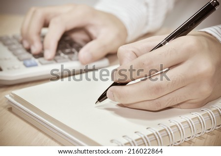 Businessman writing report and calculate on the desk in office.