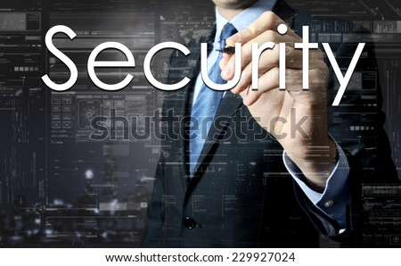 Businessman writing Security on virtual screen behind the back of the businessman one can see the city behind the window - stock photo