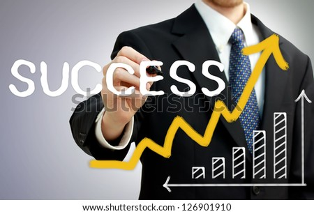 Businessman writing success with a rising arrow above a bar graph - stock photo