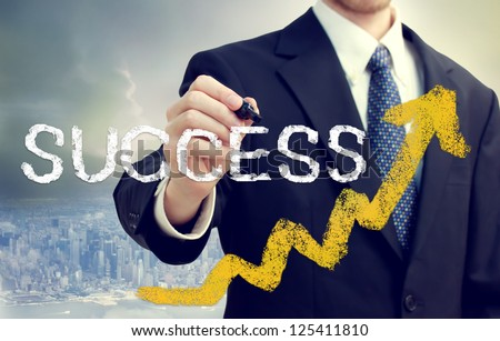 Businessman writing success with rising arrows above the city - stock photo