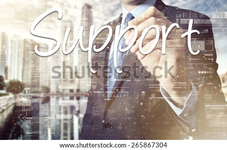 Businessman writing Support on virtual screen behind the back of the businessman one can see the city behind the window - stock photo