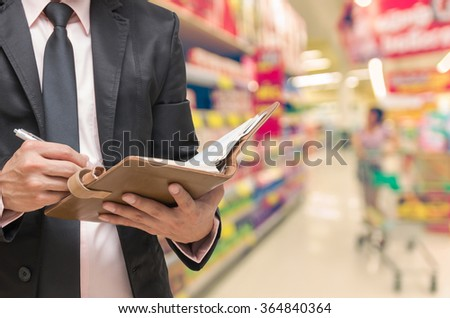 Businessman writing the note book on Supermarket blur background, business concept - stock photo