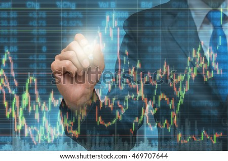 Businessman writing the trading graph of stock market on the virtual screen on photo blurred of cityscape building background, Business stock market and trading concept