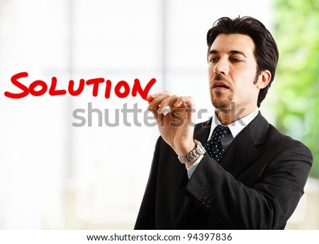 "Businessman writing the word ""solution"""