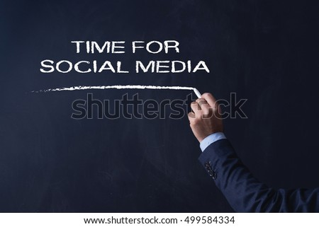 Businessman writing TIME FOR SOCIAL MEDIA on Blackboard