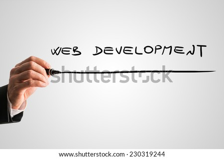 Businessman writing Web development with a black marker pen on a virtual screen over grey with plenty of copyspace.