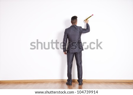 Businessman writing with a giant pencil at the white office blank wall - stock photo
