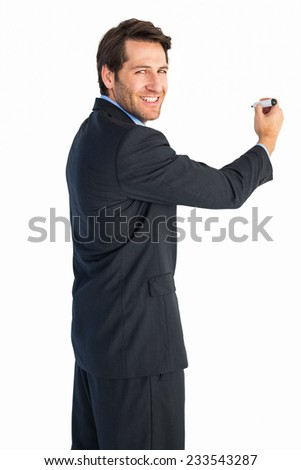 Businessman writing with marker while looking at camera on white background