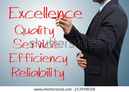 Businessman writing with pen about excellence quality service efficiency and reliability for success on virtual screen