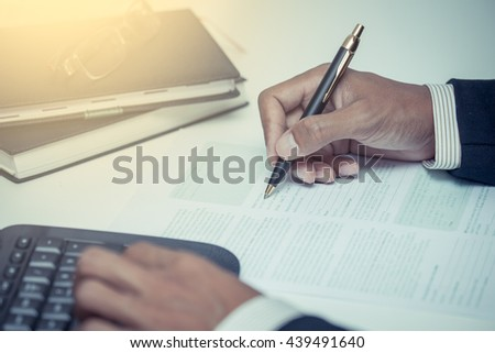 Businessman writing  with pen and working in the office in vintage color tone - stock photo