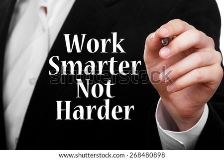 Businessman writing Work Smarter Not Harder! phrase on transparent glass - stock photo