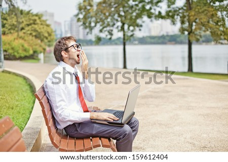 businessman yawning on a park bench - stock photo