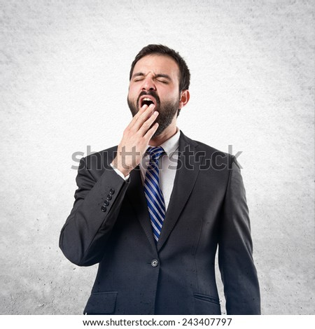 Businessman yawning over textured background