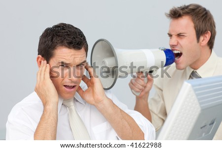 Businessman yelling through a megaphone at his colleague in the office - stock photo