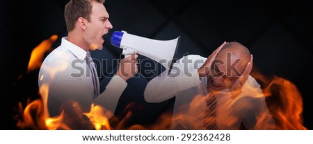 Businessman yelling with a megaphone at his colleague against dark grey room - stock photo