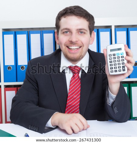 Businessmann in a black suit at office with calculator - stock photo