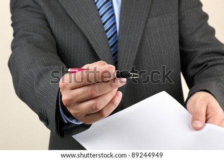 Businessmans hand holding a pen requesting a signature on a document