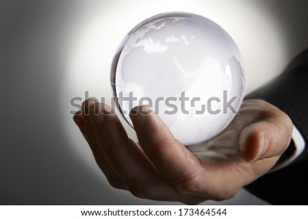 Businessmans hand holding glowing glass globe in palm against grey background - stock photo