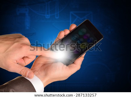 Businessmans hand holding mobile on abstract blue background
