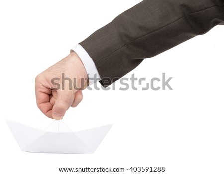 Businessmans hand holding paper boat