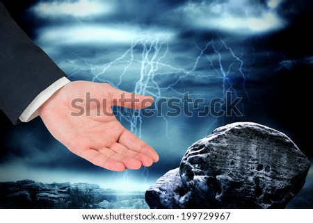 Businessmans hand presenting against large rock overlooking stormy sky