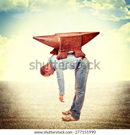 businessmanwith huge anvil on his back - stock photo