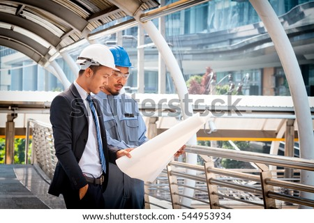 Businessmen and architect in hard hats planning construction project with office buildings