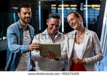 Businessmen and businesswoman discuss using digital tablet in the office - stock photo