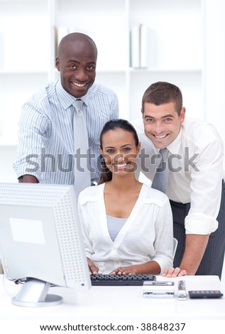 Businessmen and businesswoman using a laptop in office
