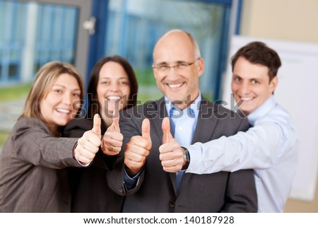Businessmen and businesswomen with thumbs up sign in office