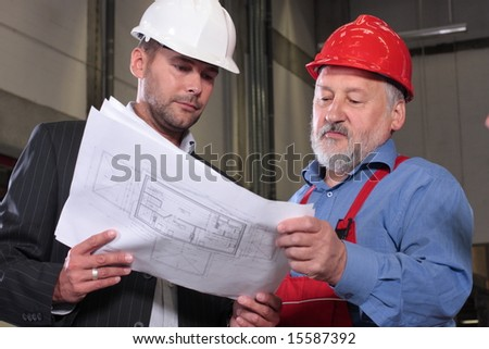 businessmen and senior worker, wearing hardhats looking at a set of blueprints and discussing a construction project. - stock photo