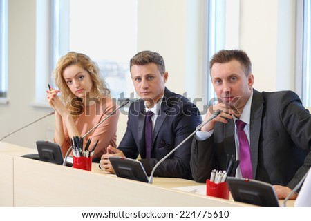 Businessmen and woman sitting in a row at the table in the conference room - stock photo