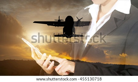 Businessmen and women are using mobile and touch smart phone for Communication and checking on plane silhouette flying in the sky on sunset ,soft focus and blurry - stock photo