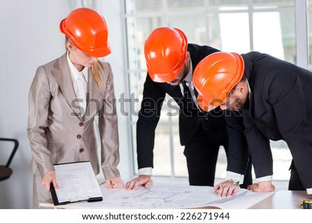 Businessmen architects create a new drawing. Three businessman architect met in the office to discuss business projects. Successful young people in the construction helmets are on the table - stock photo