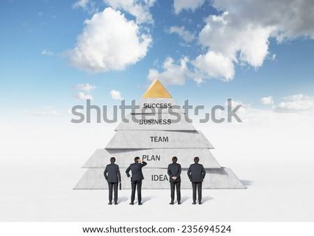 businessmen are looking at business pyramid - stock photo