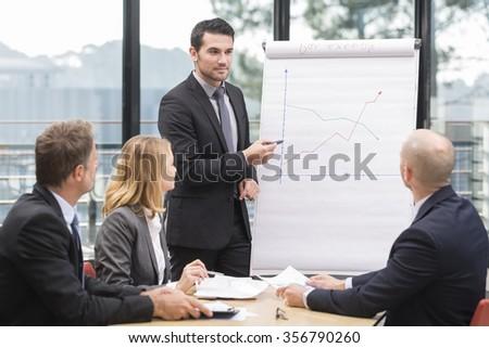 Businessmen are meeting near the flipchart - stock photo