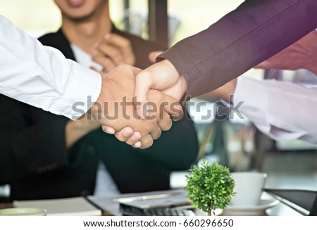 Businessmen are shaking hands with man is clapping hands