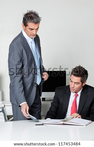 Businessmen calculating finances at desk in office - stock photo