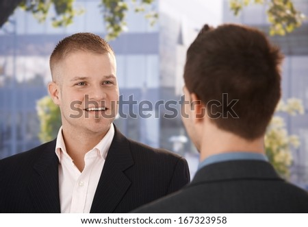 Businessmen chatting outside of office, businessman smiling at colleague. - stock photo