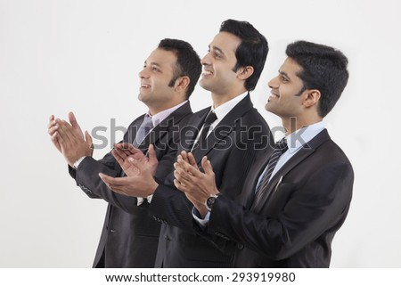 Businessmen clapping while watching cricket match - stock photo
