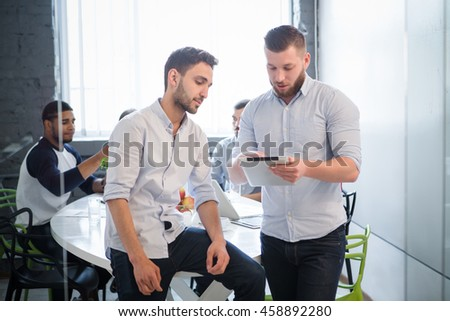 Businessmen communicating about business issues or problems in office interior. Businessman explaining new business system to his colleague. - stock photo