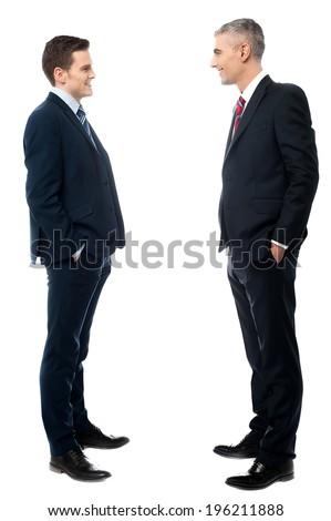 Businessmen conversation together, hands in pockets - stock photo