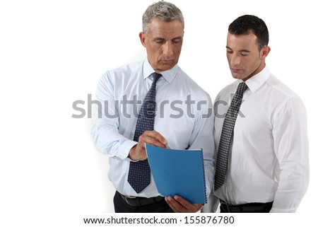 Businessmen discussing a document - stock photo