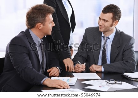 Businessmen discussing contract before sIgning, assistant waiting for document in office. - stock photo