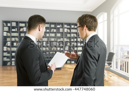 Businessmen discussing document in library interior with large bookshelf and city view. Concept of teamwork - stock photo