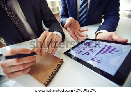 Businessmen discussing electronic data in touchpad  - stock photo