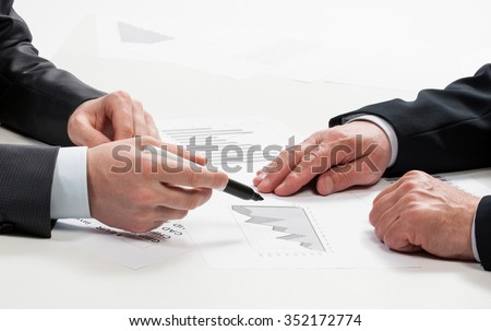 Businessmen discussing financial charts and tables during meeting