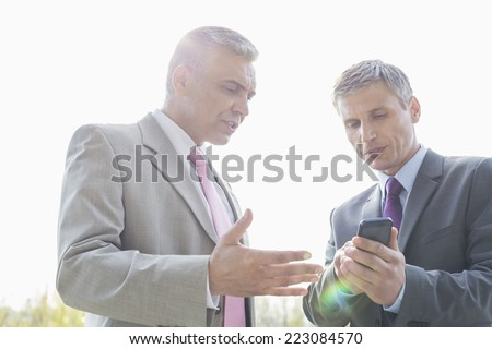 Businessmen discussing over mobile phone outdoors - stock photo
