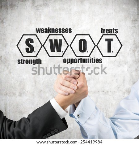 businessmen engaged in arm wrestling and drawing swot on wall - stock photo