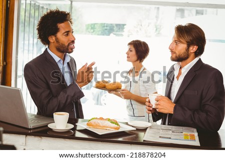 Businessmen enjoying their lunch hour at the coffee shop - stock photo